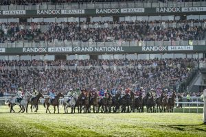 Image of all the horses lined up for the start of the Grand National nATIONAL